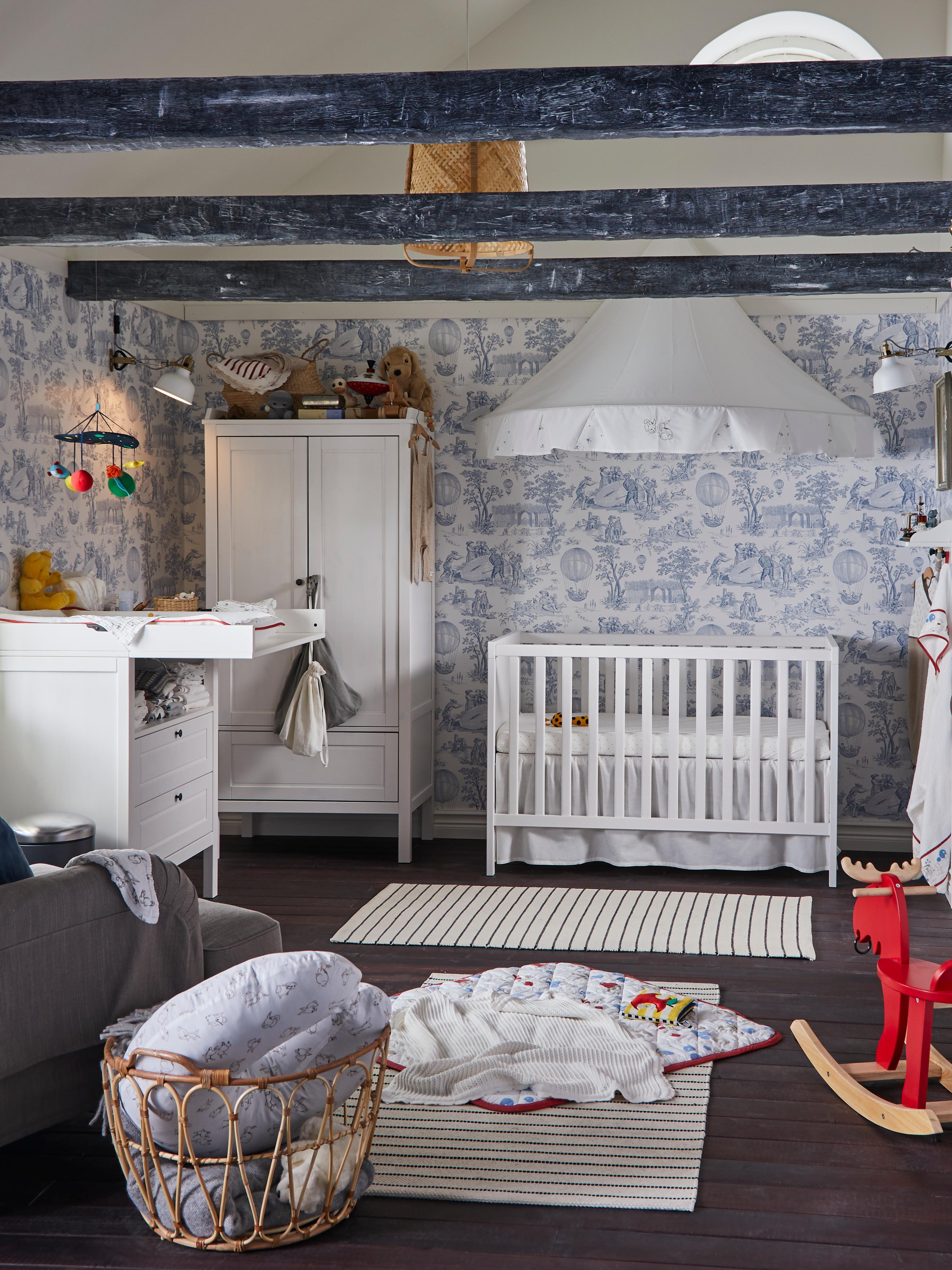 Una cuna SUNDVIK en una habitación con papel en las paredes y alfombras, un alce balancín EKORRE y mantas de bebé en el suelo.