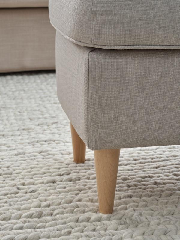 Podnóżek strandmon z drewnianymi nogami stojący na beżowym dywanie.