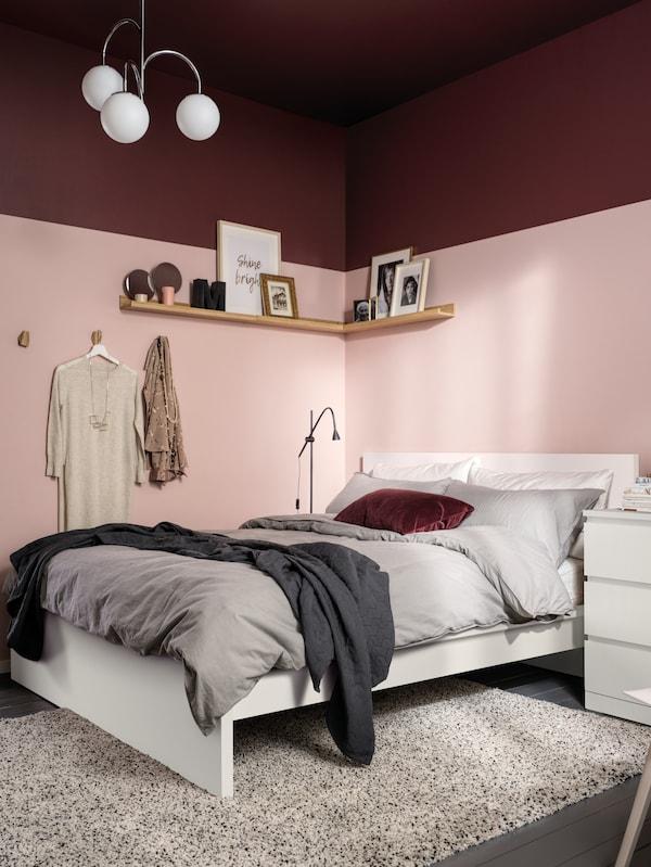 Cama MALM blanca, junto a una pared rosa, con ropa de cama ÄNGSLILJA en gris y una colcha en gris oscuro. Del techo cuelga una lámpara SIMRISHAMN.