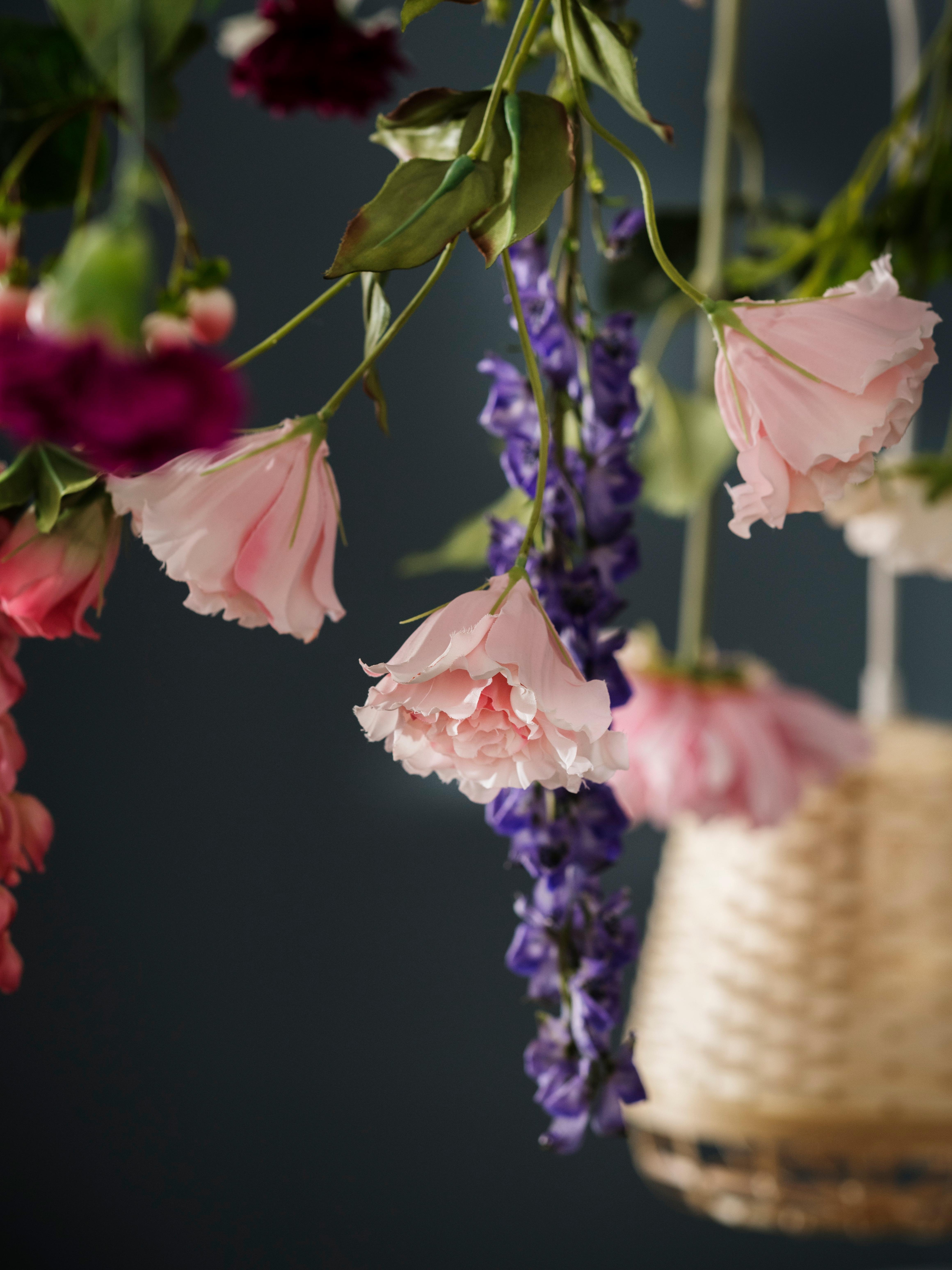 Gros plan de fleurs artificielles colorées suspendues vers le bas, avec l'accent mis sur une fleur artificielle SMYCKA Lisianthus/rose.