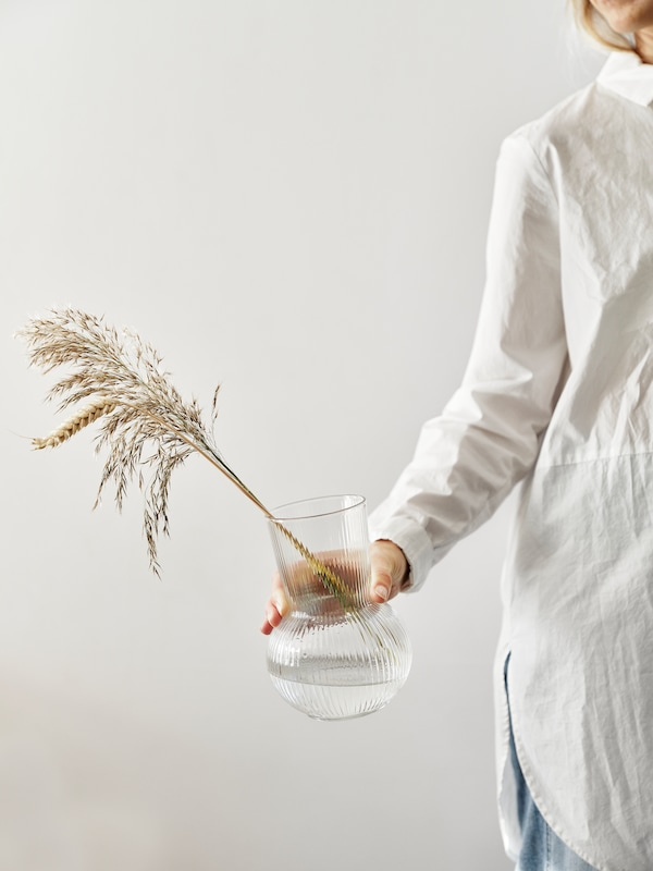 Egy víztiszta átlátszó üvegből készült PÅDRAG vázát tartó álló nőt látunk. A vázába száraz gabonaszálakat és díszfüvet állítottak.