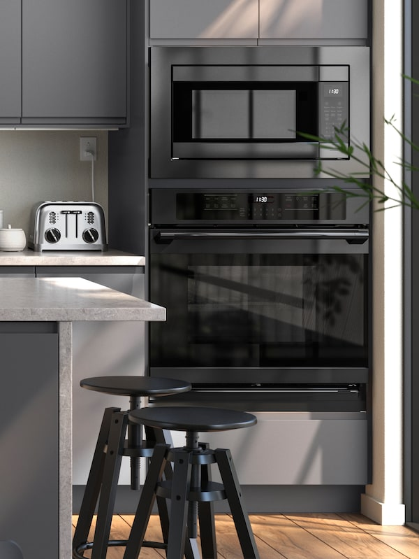 A grey VOXTORP kitchen with an ADRÄTT oven and HUVUDSAKLIG microwave, two DALFRED bar stools are next to a kitchen island.