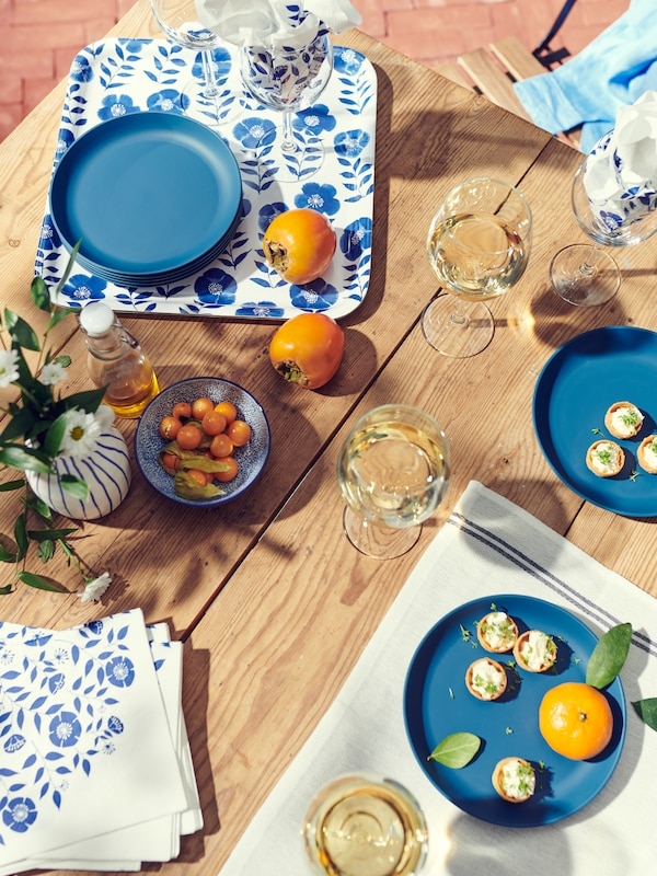 Wooden tabletop covered by SVALKA wine glasses with drinks, finger food on TALRIKA plates, and ROSENHÄTTA tray and napkins.