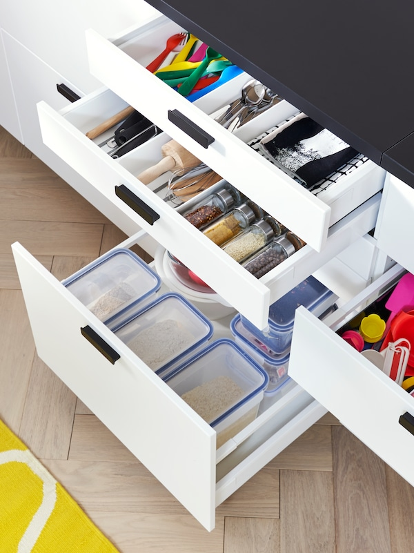 A kitchen with open white drawers displaying plastic food containers, kitchen utensils and kitchen tools inside.