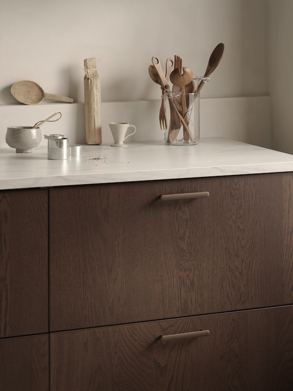 Close-up of SINARP drawer fronts, with rich oak texture and precise edging in focus.