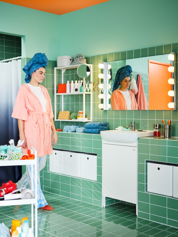 A green-tiled bathroom with a white BJÖRKÅN sink and NYSJÖN wash basin cabinet with one door and a woman wearing pyjamas.