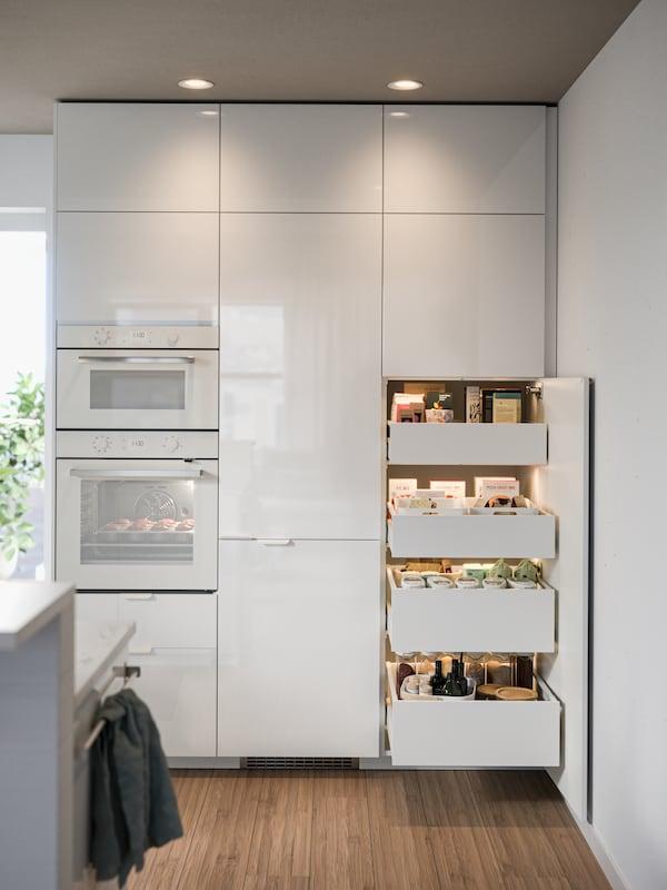 زاوية مطبخ مع مايكروويف وفرن مدمج وعدة خزائن METOD. خزانة مفتوحة تكشف عن 4 أدراج مفتوحة.