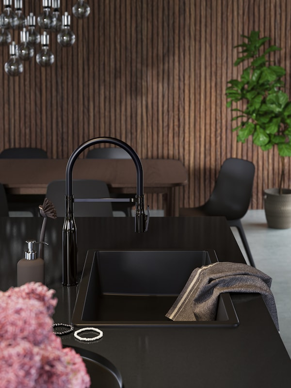 A black inset sink and tap on a black worktop on the kitchen island, a grey tea towel, black and white bracelets.