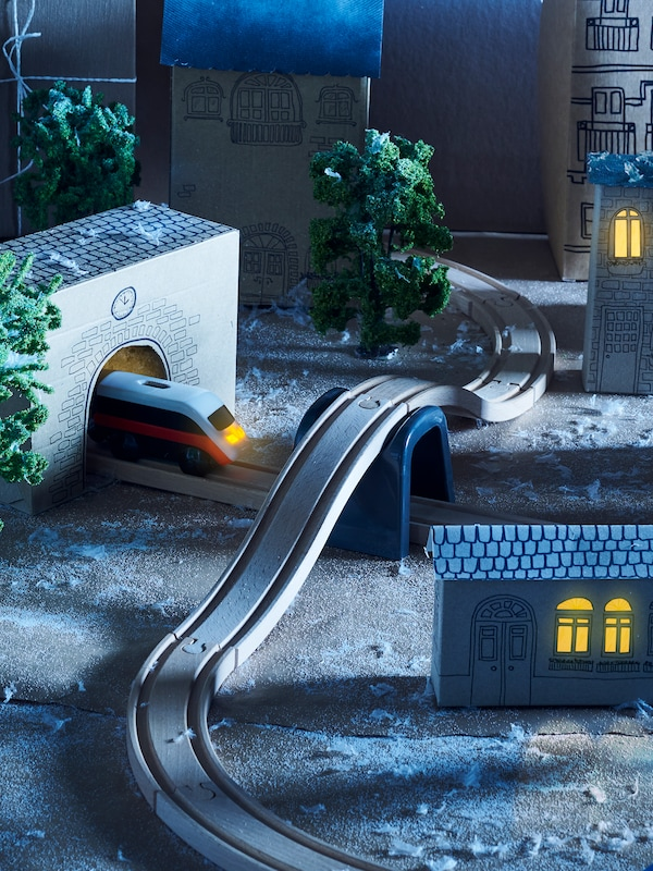 A diorama of a village made by placing a LILLABO 20-piece basic train set together with model buildings and trees.