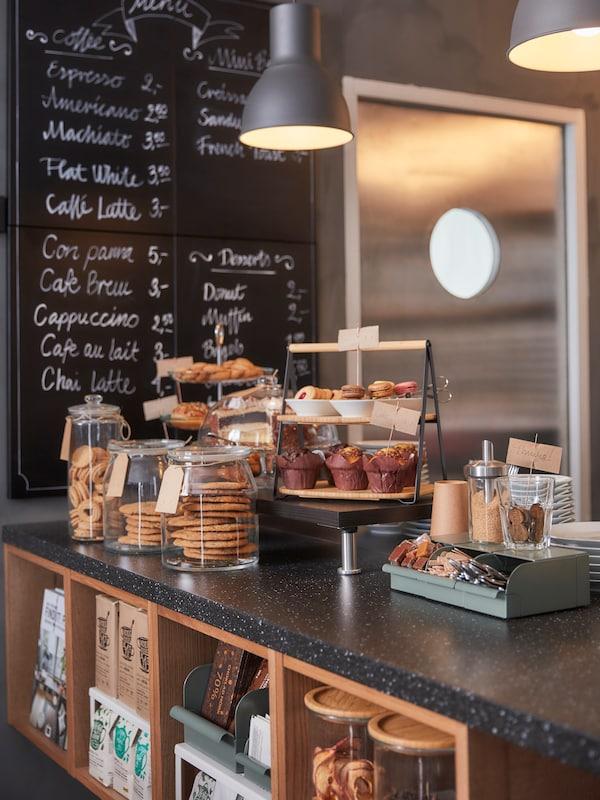 Tresen in einem Café, auf dem einige Speisen präsentiert werden. Darunter ist eine Aufbewahrung und an der Wand eine Tafel mit einer Preisliste zu sehen.