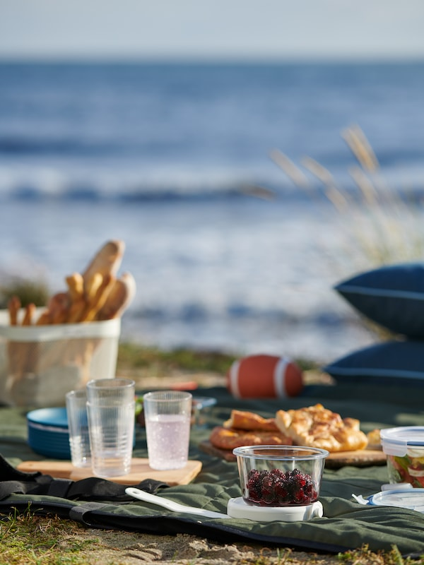 A FJÄLLMOTT picnic blanket by the sea with tableware, bread, and finger food in IKEA 365+ containers and strap-on ice packs.