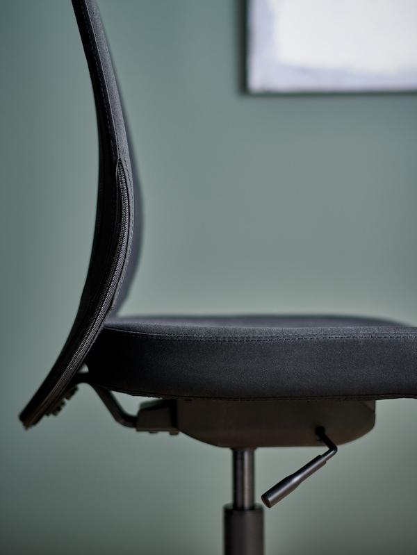 Il sedile e lo schienale di una sedia da ufficio FLINTAN nera, con una cornice sulla parete verde dietro.