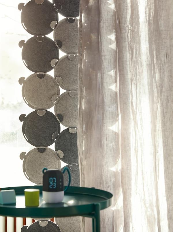 Un rideau fait de panneaux acoustiques ODDLAUG et d'un rideau transparent est suspendu à une fenêtre derrière une table-plateau GLADOM.