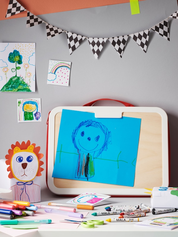 A table holding MÅLA felt tip pens and a MÅLA portable drawing case with a drawing attached. Drawings are on the wall behind.
