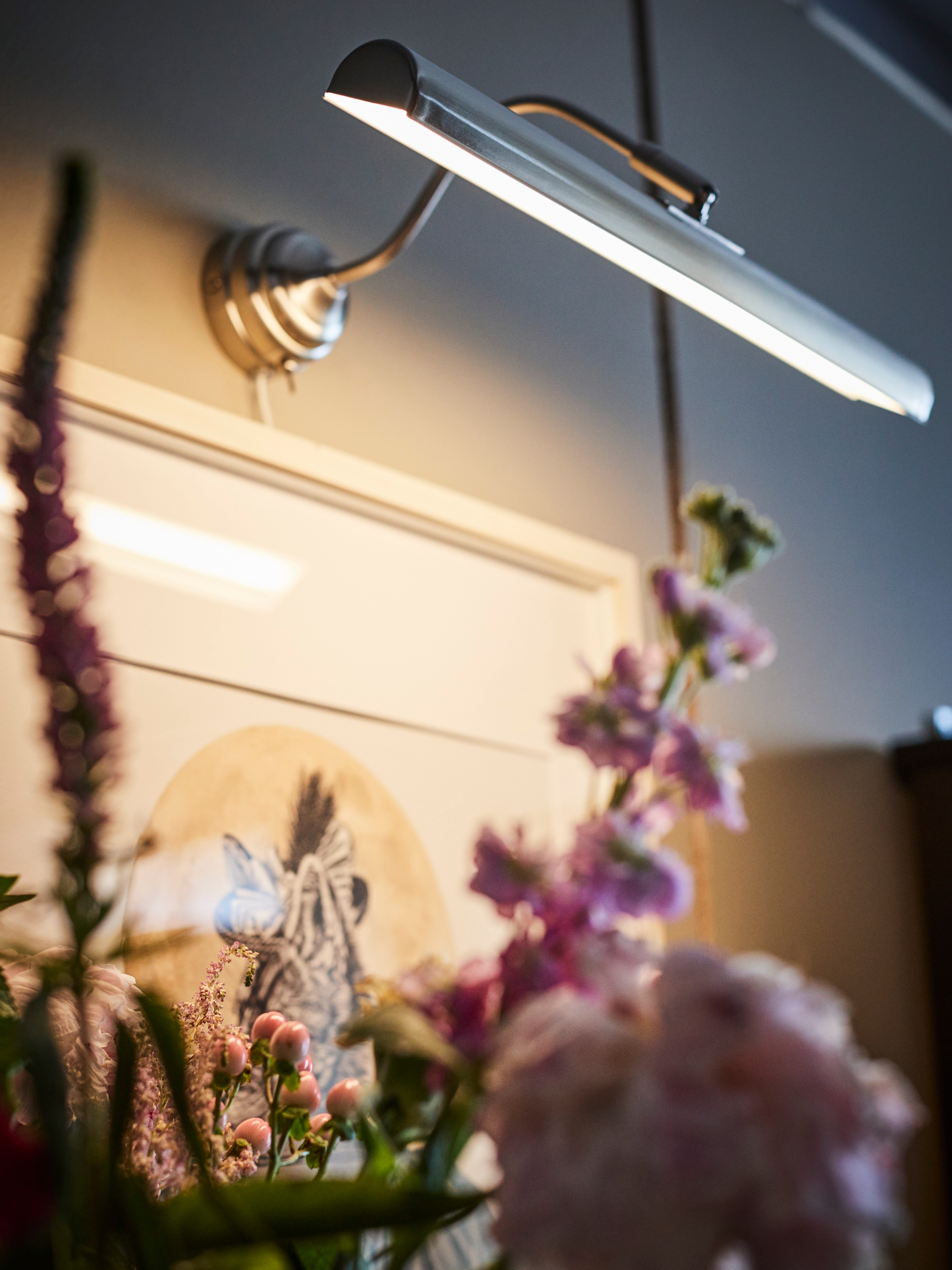 A nickel-plated ÅRSTID LED picture lighting is horizontal on a wall above a framed artwork. Flowers are in the foreground.