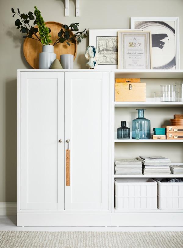 Mobile con zoccolo HAVSTA bianco di IKEA, accanto a una soluzione a giorno con piante, vasi, quadri, cestini e accessori decorativi.