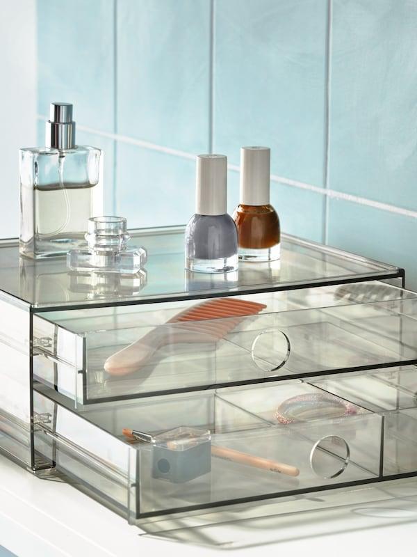 Del af et badeværelse med grønne fliser med en GODMORGON minikommode med to skuffer af røgfarvet plast fyldt med makeuptilbehør.