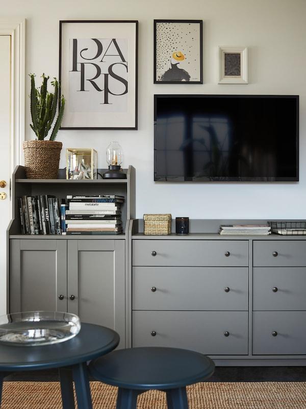 Et grått skap og to grå kommoder fra HAUGA-serien står ved siden av hverandre som en lang oppbevaringsløsning.
