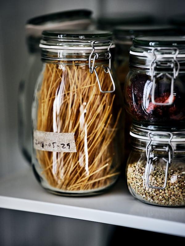 Un grand et deux petits bocaux en verre KORKEN remplis de fruits séchés, de légumineuses et de pâtes, sur une tablette blanche.