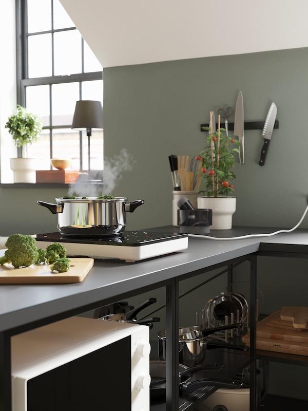 Šedá pracovní deska s černo-bílou přenosnou indukční varnou deskou, hrnec z nerezové oceli, prkénko a brokolice.