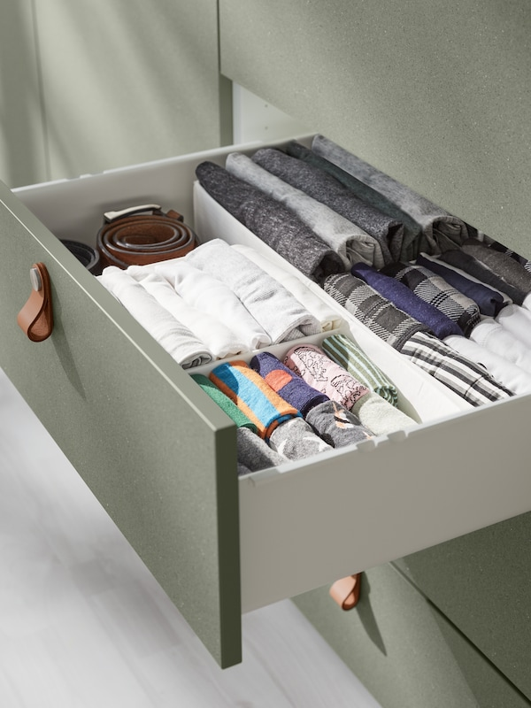 Cassetto di un guardaroba PLATSA aperto. All'interno del cassetto ci sono molti capi piegati, tra cui calze e biancheria intima.
