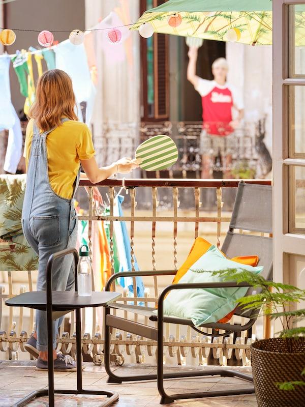 Una ragazza con in mano una racchetta da spiaggia è appoggiata sulla ringhiera del balcone di casa. Luci e indumenti appesi sullo sfondo.