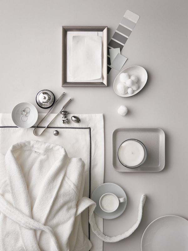 Egy fehér ROCKÅN fürdőköpeny, fehér/sötétszürke ágynemű, egy kis ezüst keret, fehér tálak és csészék cukorkákkal és gyertyákkal.