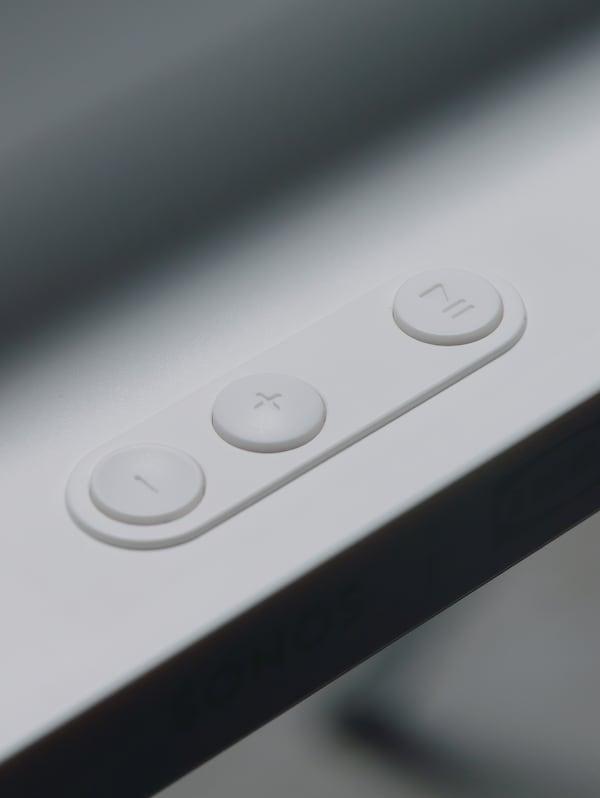 Gros plan du panneau de commande avec boutons de lecture/pause et de réglage de volume d'un cadre avec enceinte WiFi SYMFONISK en blanc.