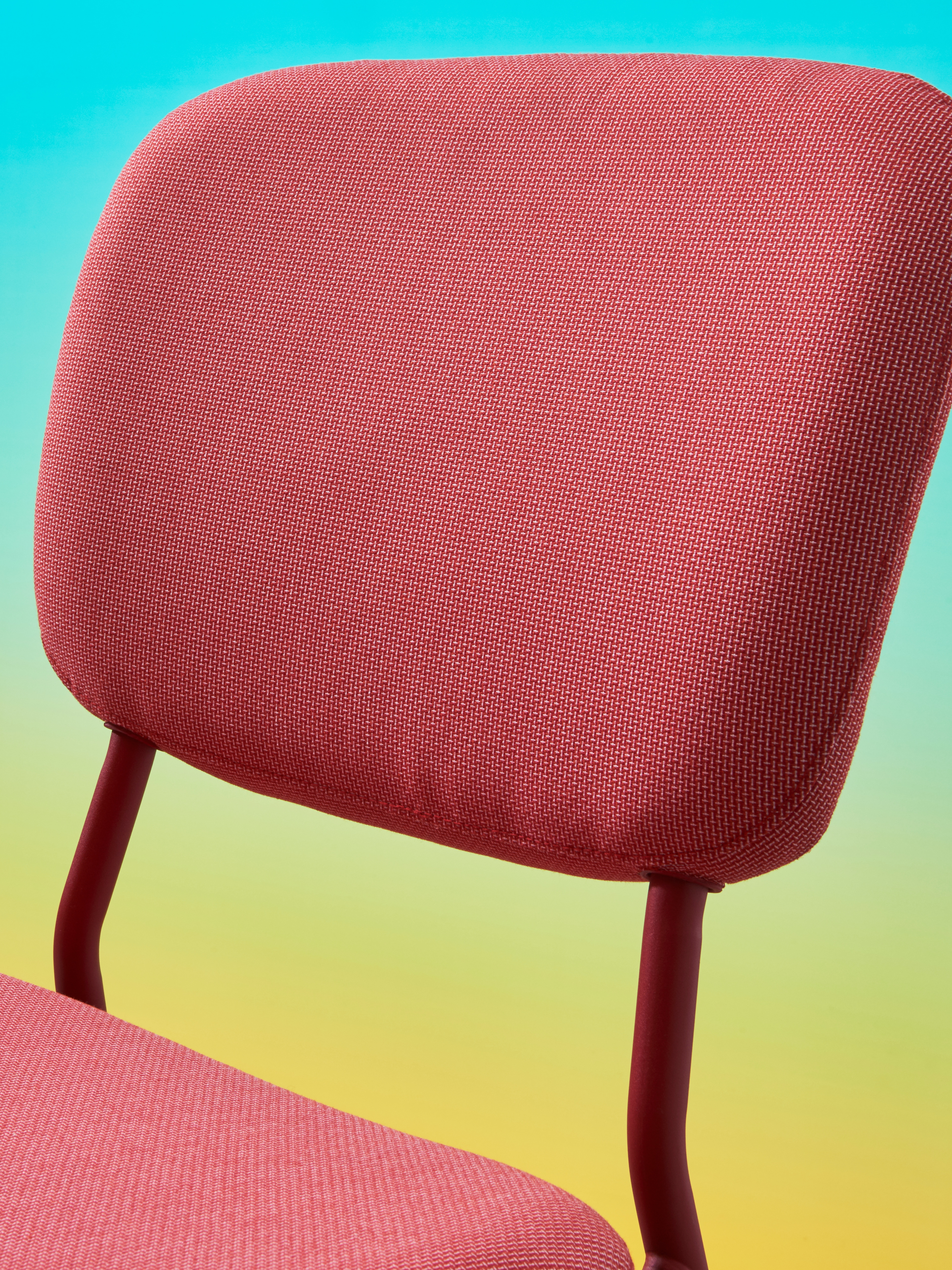 Close-up of a KARLJAN chair in red, against a blue and yellow background, showing the upholstered backrest and metal frame.