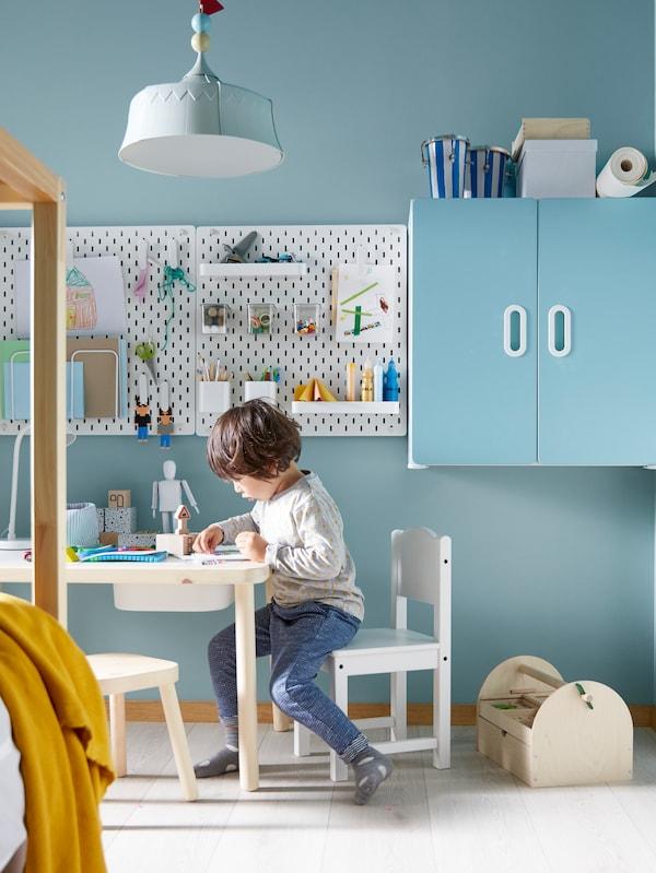 Ein Kind sitzt auf einem SUNDVIK Kinderstuhl an einem FLISAT Kindertisch und ist gerade sehr beschäftigt. Darüber hängt eine TROLLBO Hängeleuchte.