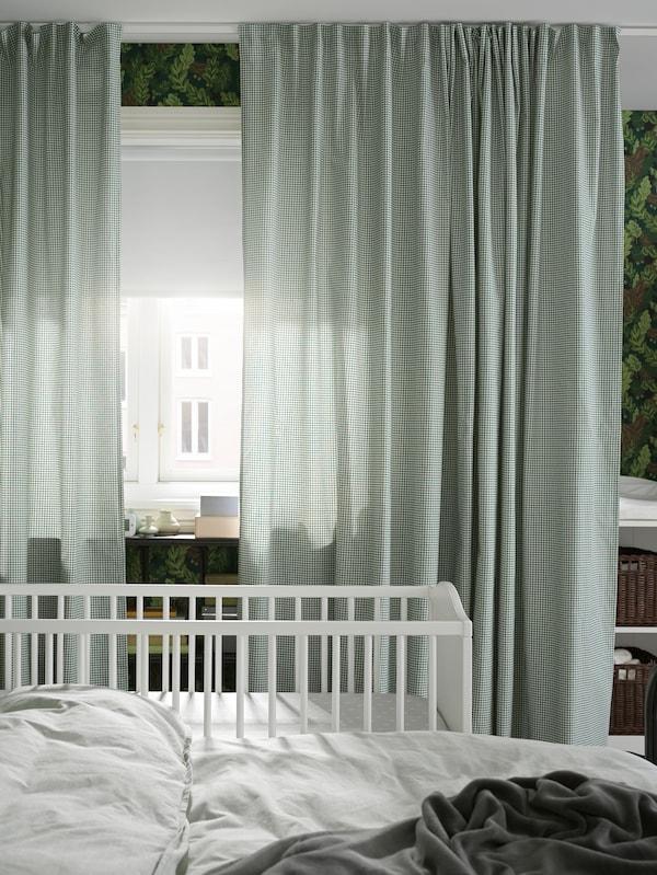 Lângă fereastra cu draperii verzi/albe se află un pat și un pătuț, iar un stor opac alb este pe jumătate ridicat.