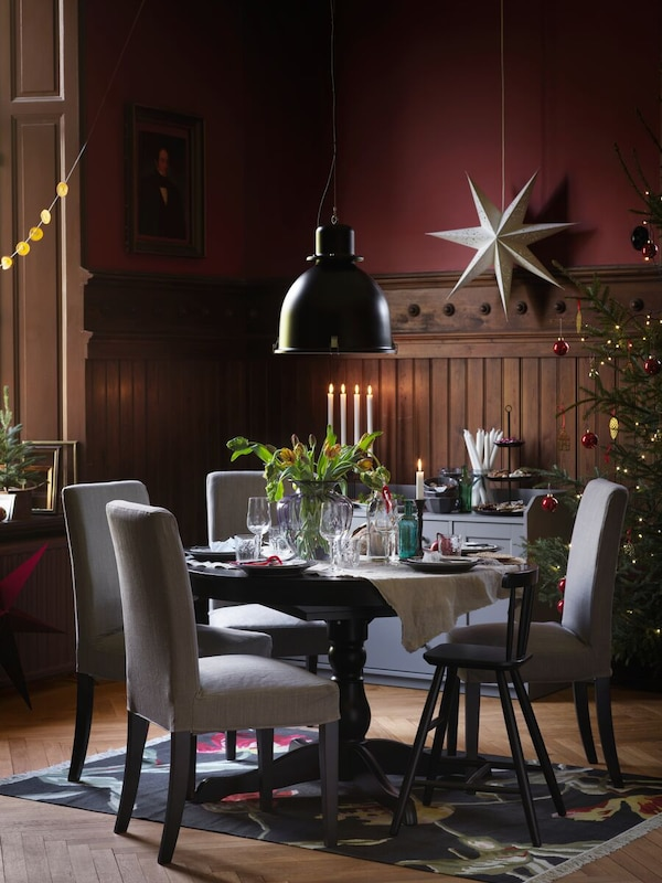 A round black INGATORP table set for a festive meal. A SVARTNORA pendant lamp is over the table and a star is behind it.