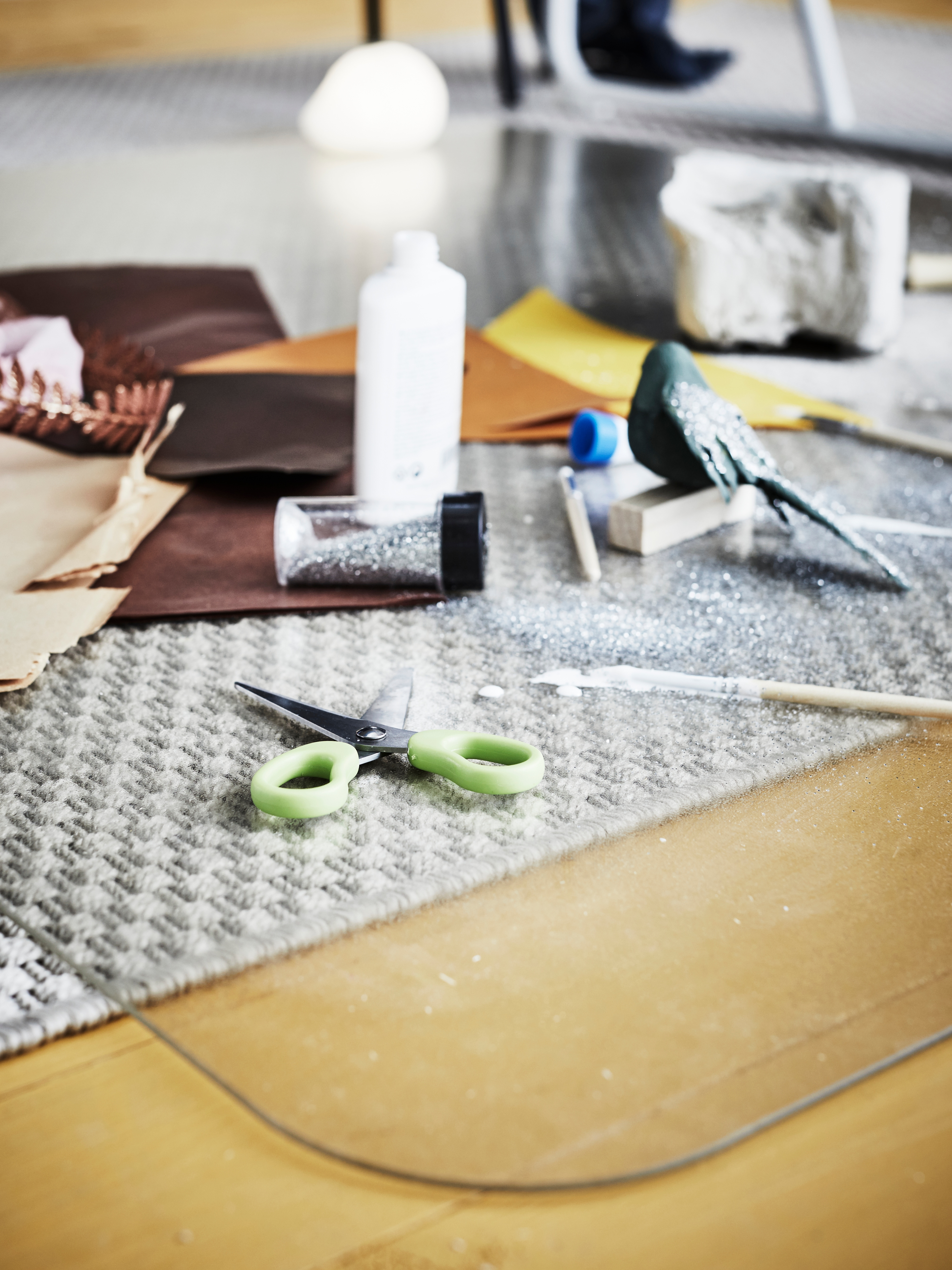 Drawing, painting and art supplies strewn across a plastic, transparent KOLON floor protector over a rug on a wooden floor.