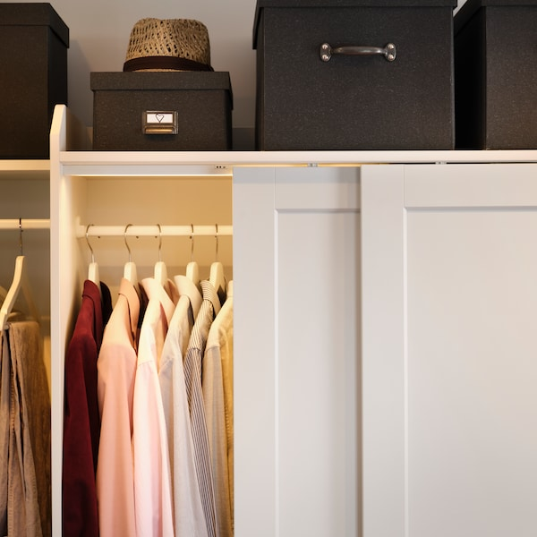 A HAUGA wardrobe combination with an open sliding door and clothes inside. Black boxes and a hat sit on top of the wardrobe.