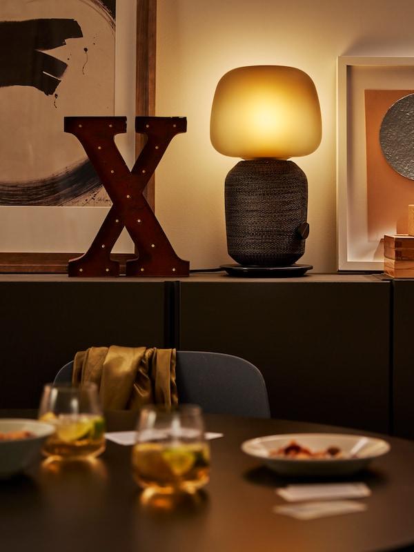 En sort SYMFONISK lampe står på en sort kommode ved siden af et stort X. I forgrunden ser man noget af et spisebord med glas og tallerkner.