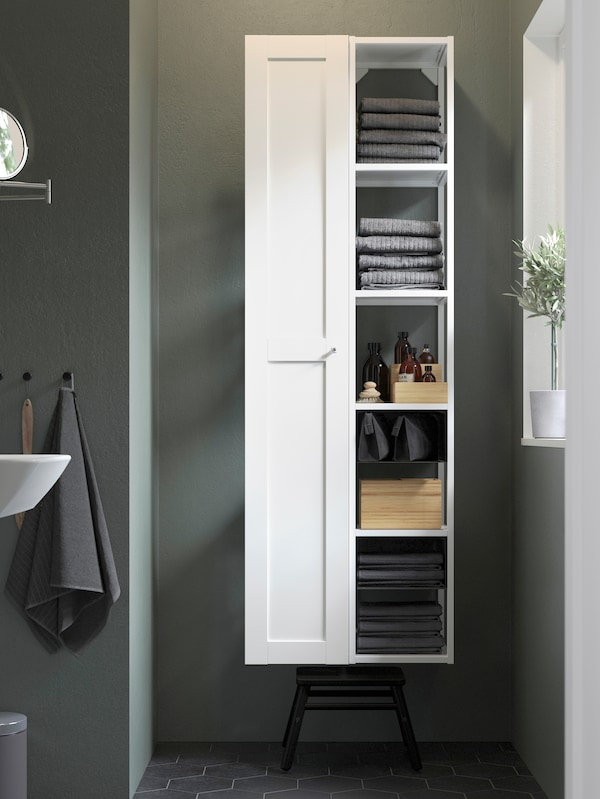 A white wall cabinet with one door and open shelves beside it for various bathroom products.