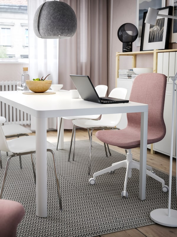 An open laptop on a white TINGBY table with grey pendant, five white chairs and a pink office chair on a patterned rug.
