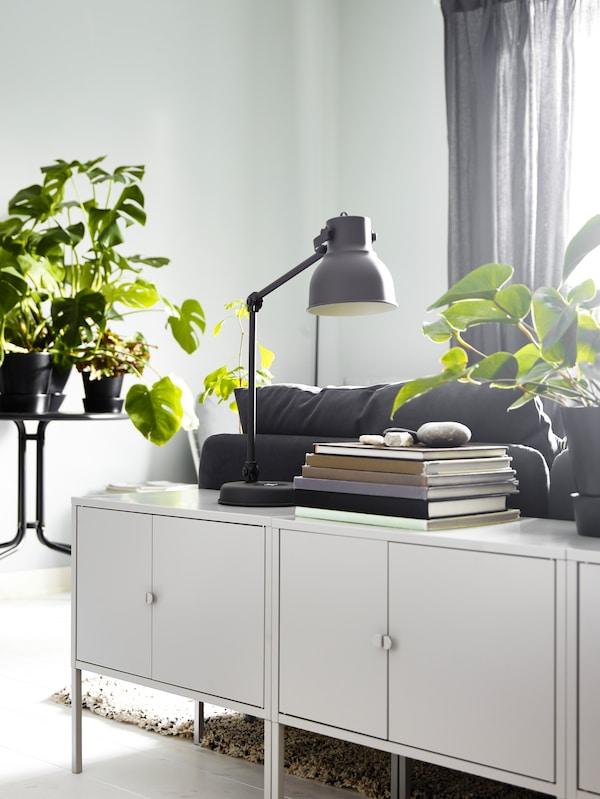 Ett par moderna LIXHULT skåp i metall/grått bakom soffan smälter in bland den övriga inredningen.