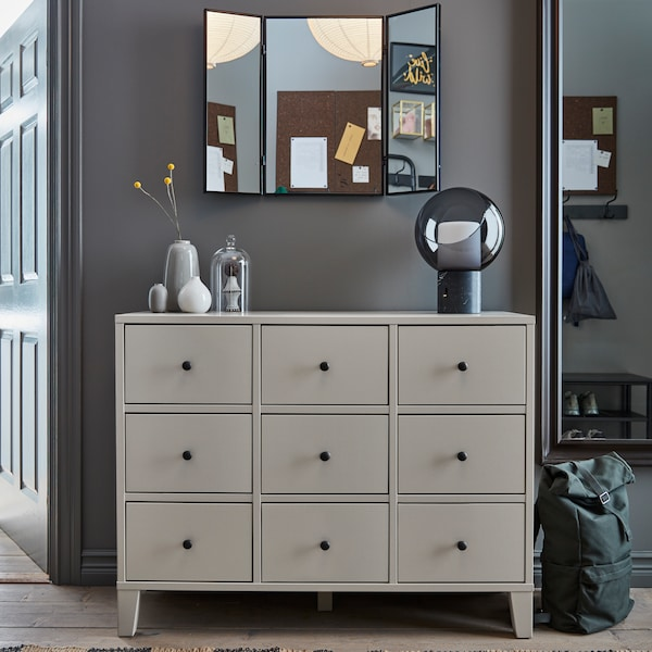 A hallway with a grey BRYGGJA chest of drawers, with vases on top. A triple mirror above and a large mirror beside it.