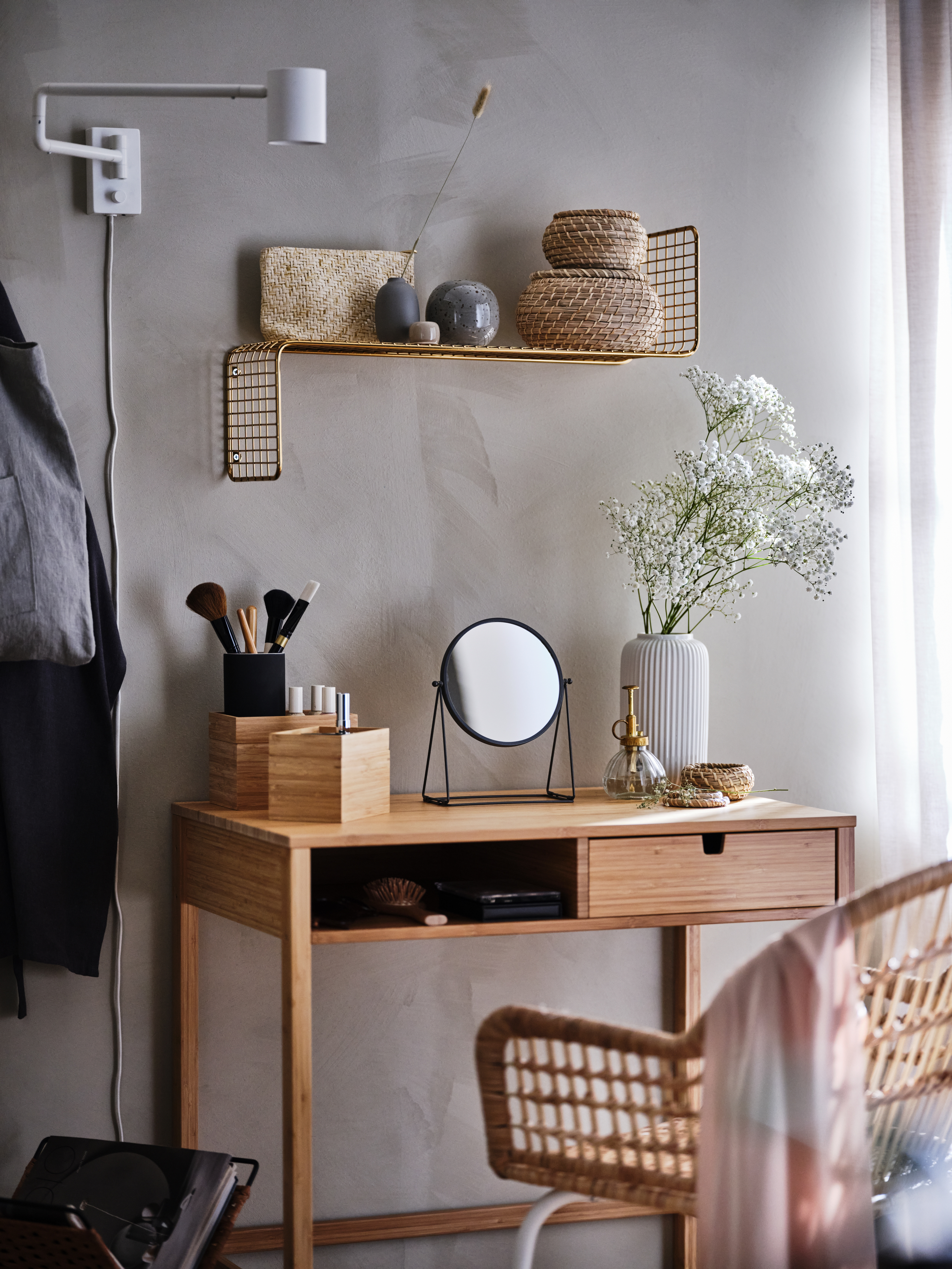 Beauty corner with a LASSBYN mirror, a vase with flowers and make-up accessories in DRAGAN bamboo boxes, set on a small desk.