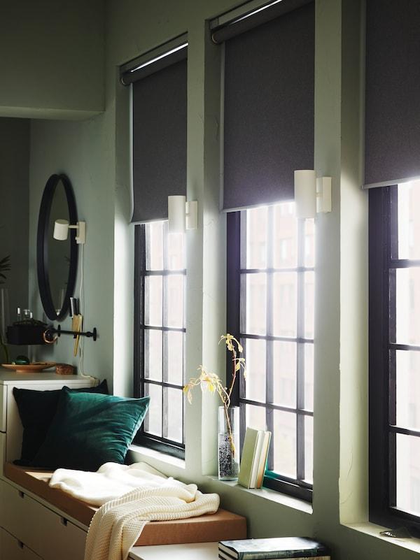 Tre vinduespartier med rullegardin halvt rullet op. Der strømmer lys ind i et rum med grønne vægge og en lav kommode brugt som en bænk står under vinduerne.