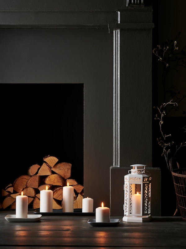 A black fireplace with stacked wood inside with lit white block candles in front along with a white lantern.