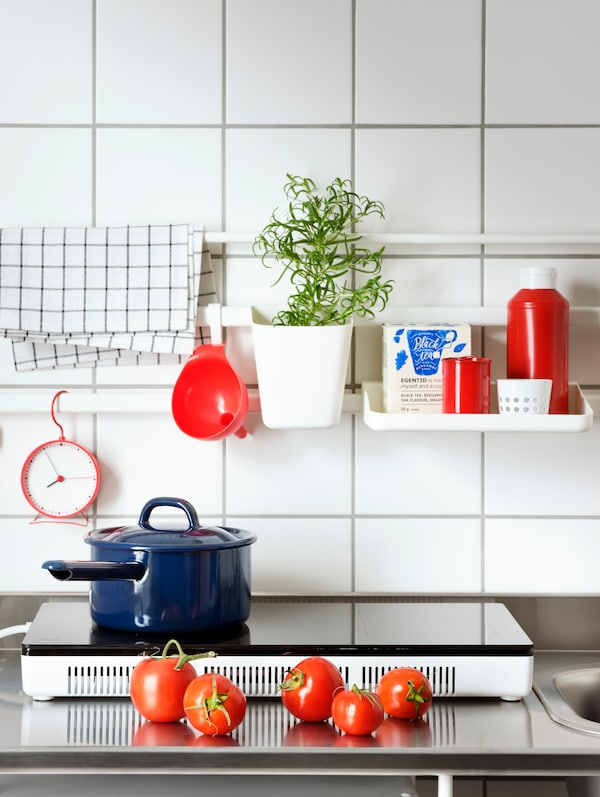 A TILLREDA portable induction hob with a blue saucepan, kitchen items on a white SUNNERSTA shelf and a container with herbs.