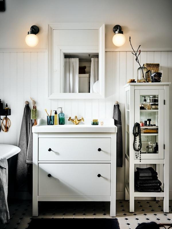 Un meuble lavabo HEMNES/RÄTTIVIKEN avec deux tiroirs dans une salle de bain ensoleillée blanche de style campagnard, surmonté d'un miroir et d'appliques murales.