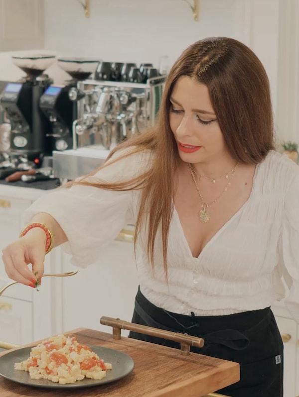 Egy fehér blúzos nő egy tányér frissen főtt tésztára zöld fűszert szór.