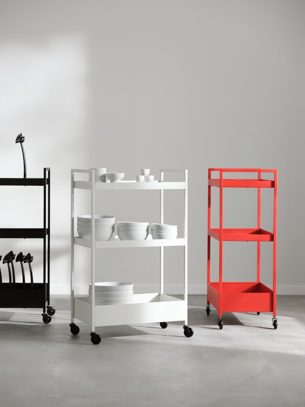 Three NISSAFORS trolleys beside each other. One is black, one is white and one is red. The white one has bowls on each shelf.