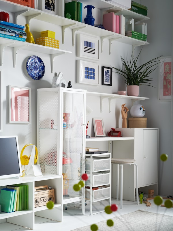 A living room wall with white shelves, white BAGGEBO cabinet with glass door, white LENNART drawer unit and MARIUS stool.