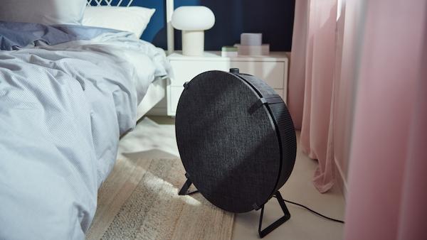 Egy hálószobában egy fekete, földre állítható STARKVIND típusú légtisztító áll a padlón az ágy és az ablak között.