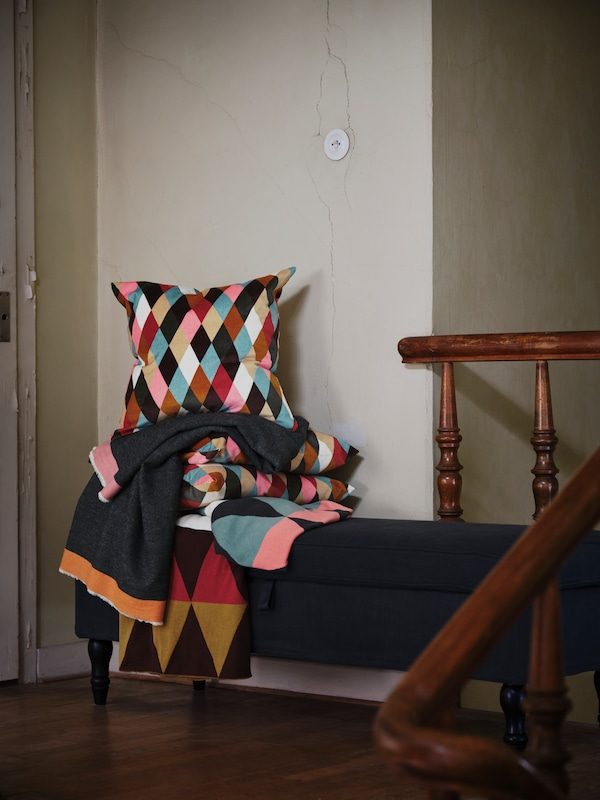 Diamond-patterned DEKORERA blankets and cushions in bright colors are piled on top of a bench by a set of stairs.