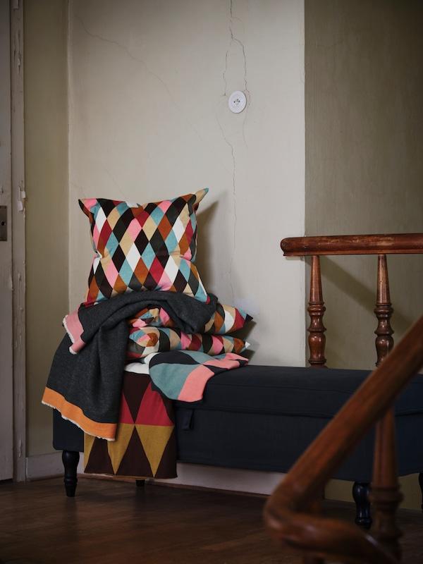 Des couvertures et des coussins DEKORERA à losanges de couleurs vives sont empilés sur un banc, près d'un escalier.